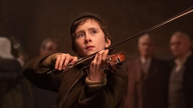 Un jeune garçon joue du violon.