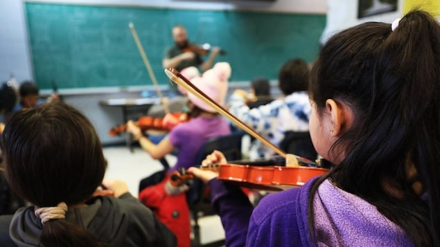 Des jeunes qui jouent du violon dans une classe