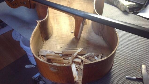 Un violoncelle en morceaux contenant de nombreuses éclisses de bois et posé sur une table.