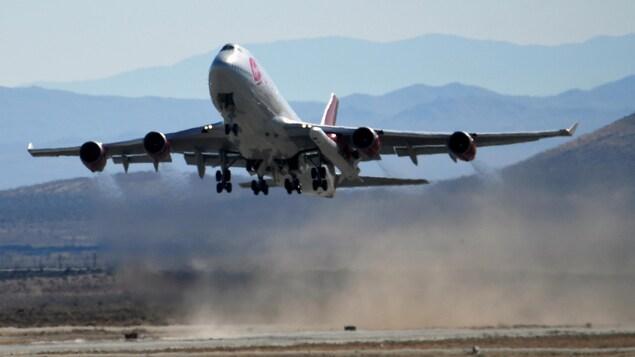 Un avion portant une fusée sous son aile gauche décolle d'une piste d'aviation. On aperçoit des collines arides à l'arrière.