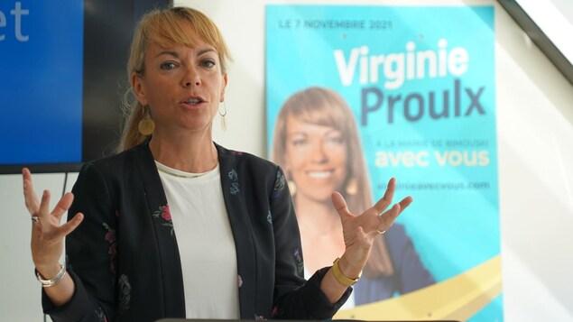 Virginie Proulx derrière un lutrin lors d'une conférence de presse pendant la campagne électorale.