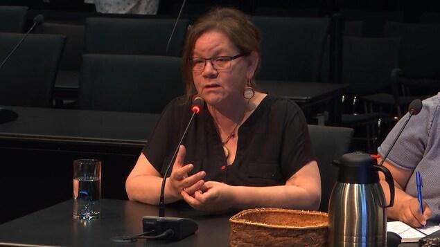 Une femme aux cheveux bruns qui sont attachés porte des minces lunettes noires et parle dans un micro noir posé sur le bureau devant elle.