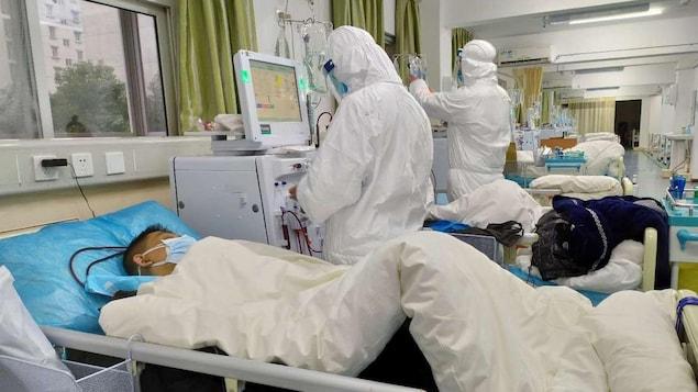 Un patient alité avec deux travailleurs de la santé qui portent des uniformes de protection.