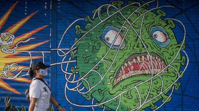 Une femme masquée passe devant une murale d'un virus qui a l'air menaçant.