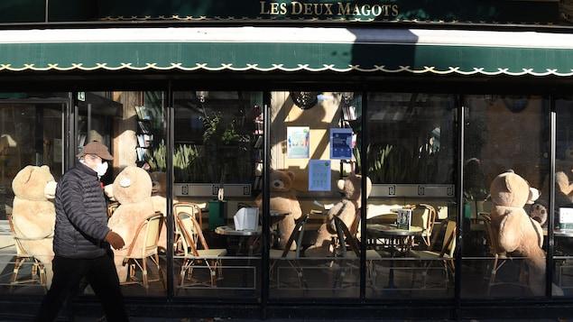 Un homme passe devant le café Les Deux Magots, à Paris.