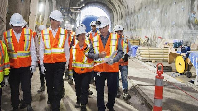 M. Trudeau et Mme Plante, entourés d'autres dignitaires, regardent les travaux.