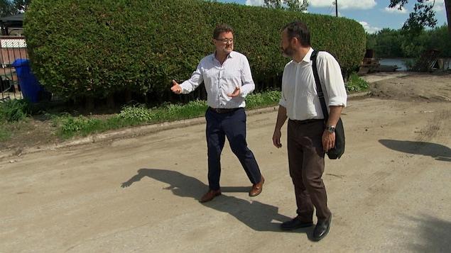 Les deux hommes marchent dans une rue longeant un cours d'eau.