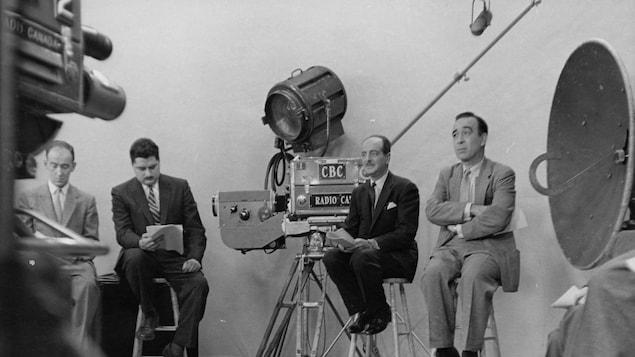 Sur des tabourets, des journalistes, dont Raymond Charette et Lucien Côté, révisent leurs notes entourés de caméras et d'autre équipement technique.