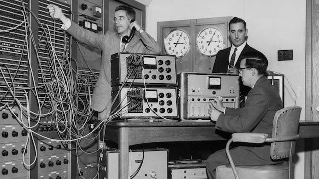 Lors de la visite royale, trois techniciens s'affairent dans une régie centrale de radio.