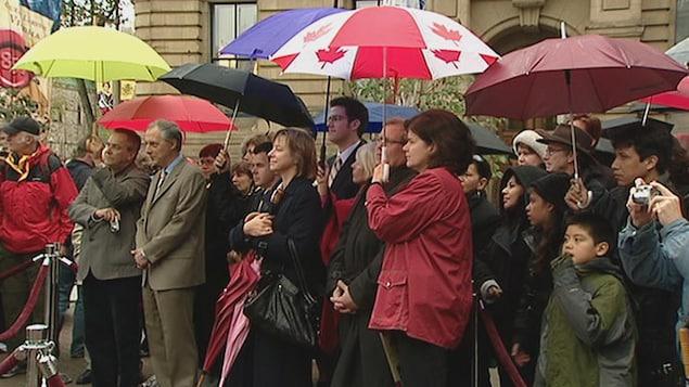 Des personnes qui attendent sous la pluie derrière un ruban rouge. La plupart ont des parapluies et certains tiennent un appareil photo.