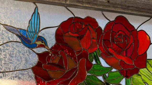 Un vitrail représentant un colibri butinant un rose rouge.