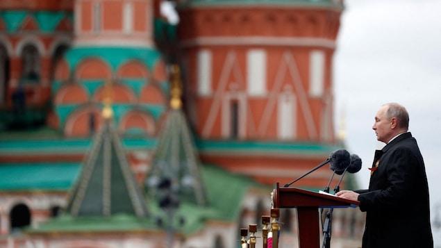 Le président russe Vladimir Poutine prononce un discours avec en arrière-plan les bâtiments emblématiques de la Place rouge à Moscou.