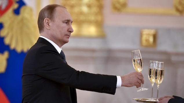 Vladimir Poutine se sert un verre de champagne.