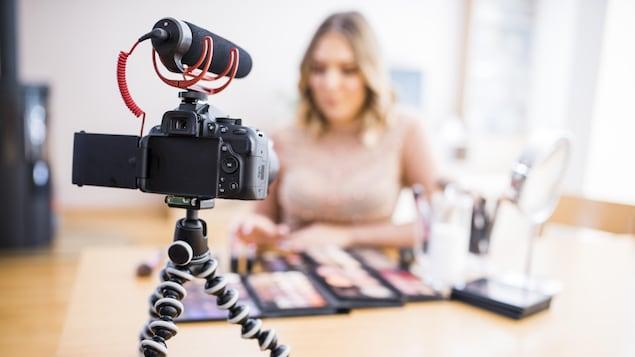 Une femme se filme en train de tester des produits de beauté.