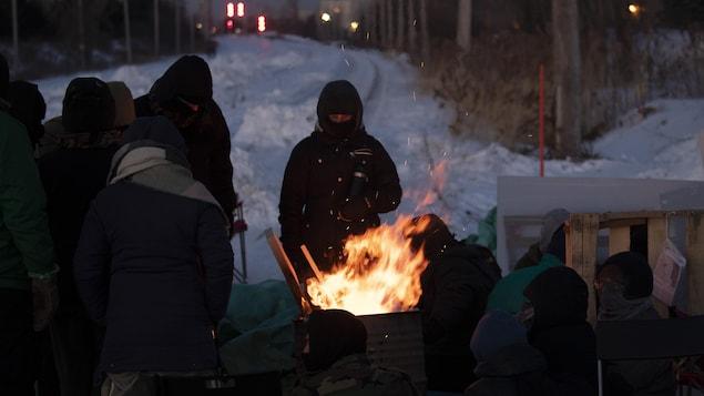 Des manifestants se réchauffent auprès d'un feu.