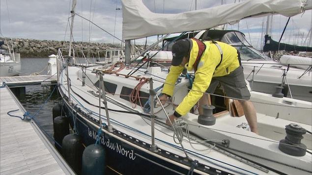 Un plaisancier prépare son voilier pour une sortie en mer.