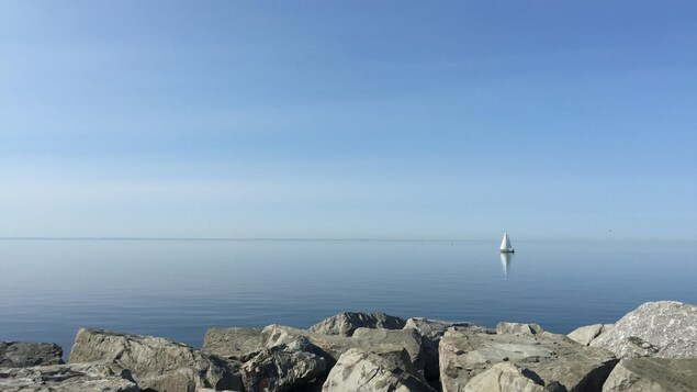 Un voilier navigue sur un fleuve calme en face de Rimouski