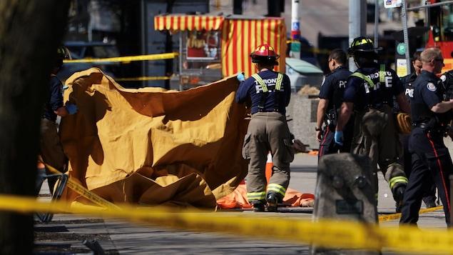 Des pompiers couvrent une victime happée par une fourgonnette, qui a heurté plusieurs personnes à Toronto.
