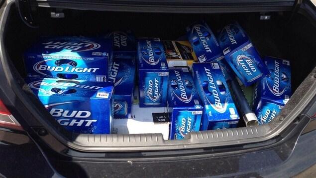 Le coffre d'une voiture rempli de caisses de bière.