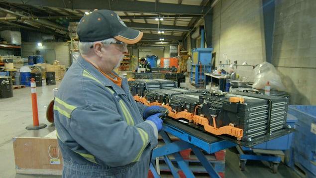 Un homme se met au travail dans une usine de recyclage.