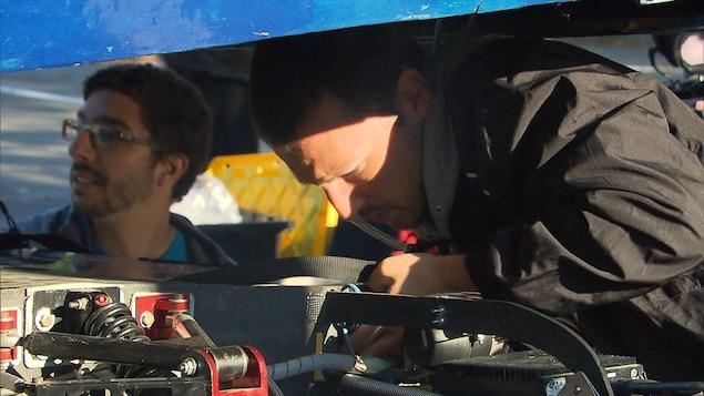 Un étudiant fait des vérifications techniques sous la coque de la voiture solaire.