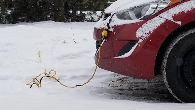 Un fil électrique va jusqu'au capot d'une voiture stationnée dans une rue enneigée.