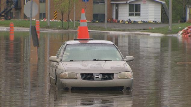 Une voiture inondé avec un cône orange sur le toit.