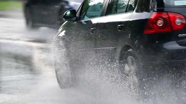 Une voiture conduit dans une flaque d'eau.