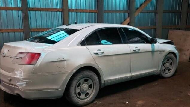 Une Ford Taurus 2013 blanche dans un entrepôt.