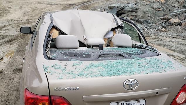 Une voiture dont le toit s'est écrasé et dont la vitre arrière est éclatée.