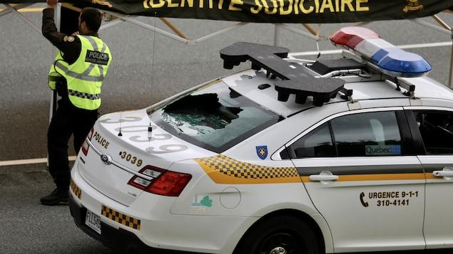 La vitre arrière d'une voiture de la policière est fracassée par un projectile.