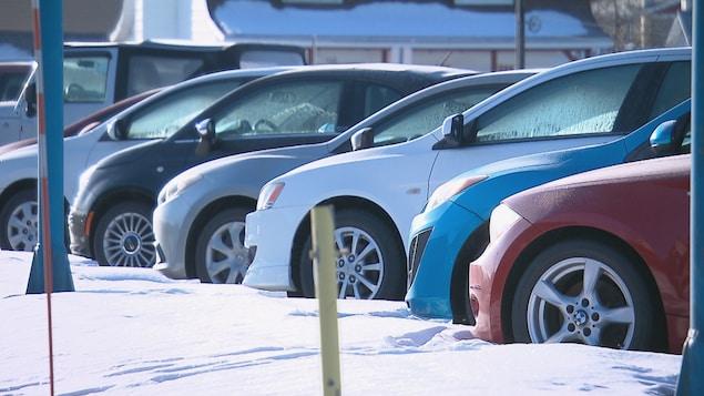 Des véhicules stationnés sont photographiés une journée d'hiver. De la neige est vue au sol.
