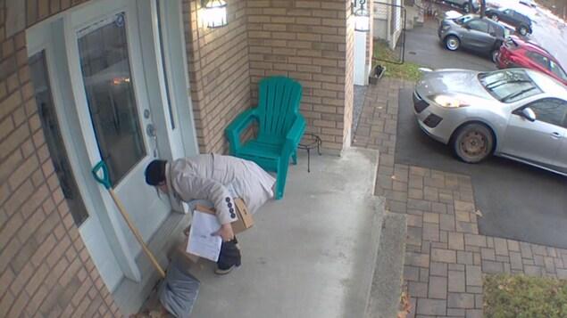 Une femme ramasse des colis devant la porte d'une maison.