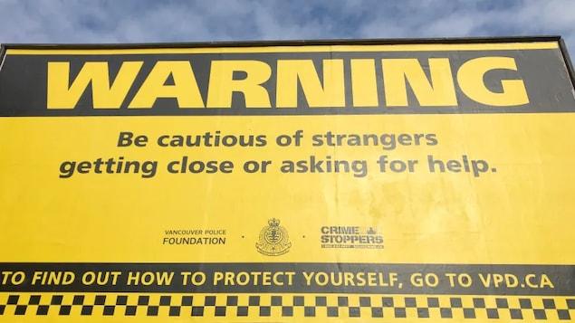 Un panneau publicitaire où l'on peut lire : attention, soyez vigilants lorsque des étrangers se rapprochent de vous ou vous demandent de l'aide.