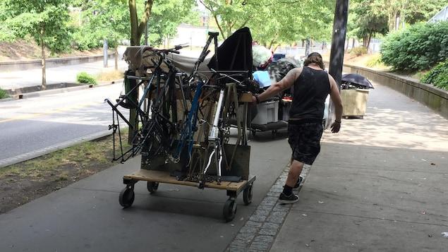 Un homme traîne un chariot avec des cadres de vélos.