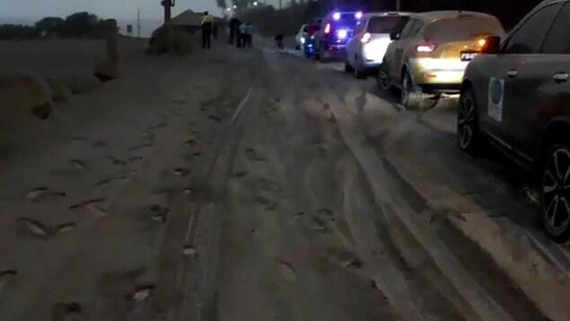 Des  véhicules roulent sur une route recouverte par une épaisse couche de cendres.