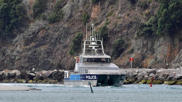 Un bateau de la police près d'un flanc rocheux