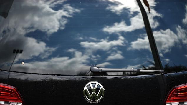 Le reflet du ciel nuageux sur la vitre arrière d'un véhicule du constructeur automobile allemand Volkswagen (VW).