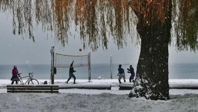 Des passionnés de volley-ball jouent sur une plage enneigée de Vancouver