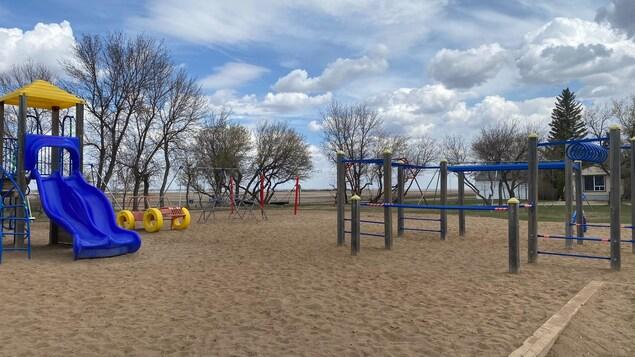 La cour de l'école Providence de Vonda est composée de sable et d'installation de jeux de gymnastique et de glissoires. Elle est délimitée par des arbres. Au loin, on voit la prairie.