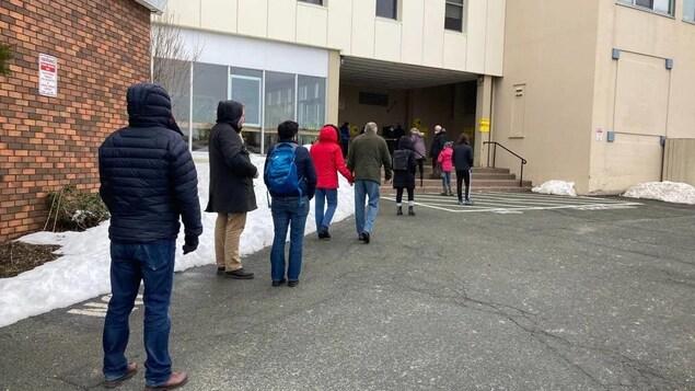 Des électeurs en rang à l'extérieur devant un bureau de vote par anticipation.