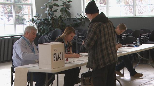 Un homme s'inscrit pour voter. Il y a un homme et une femme qui lui parlent.