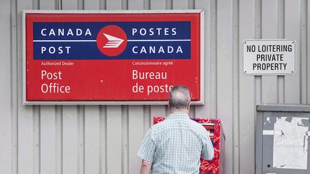 Un hombre coloca un sobre en un buzón de correos.
