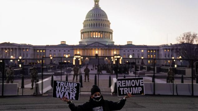 Un homme portant un t-shirt sur lequel on peut lire « Trump est un danger pour nous tous » tient deux pancartes anti-Trump devant le périmètre de sécurité protégeant le Congrès