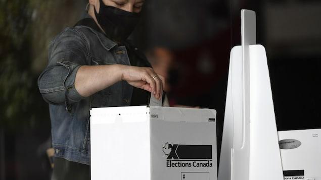 Un homme dépose son bulletin de vote dans l'urne à l'effigie d'Élections Canada.