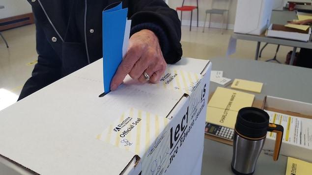 Un homme glisse un bulletin de vote dans la fente d'une boîte de scrutin.
