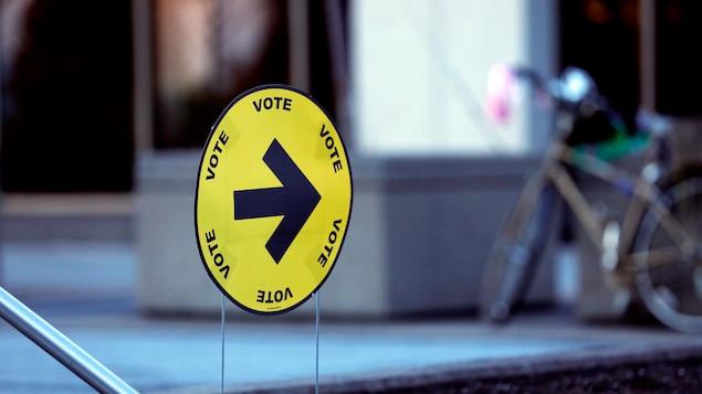 Une flèche indique l'entrée d'un bureau de vote.