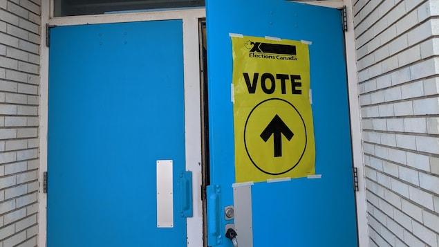 Gros plan sur une porte extérieure bleue entrouverte et sur laquelle est apposée une affiche jaune sur laquelle on peut lire Élections Canada Vote.