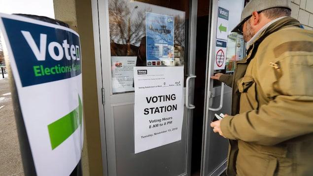 Un homme ouvre une porte où est placardée une affiche disant qu'il s'agit d'un bureau de vote ouvert de 8 à 20 heures.