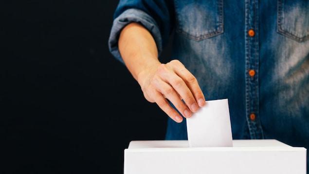 Un électeur qui tient un bulletin et le glisse dans l'urne.